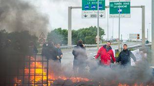 Des marins de la compagnie MyFerryLink brûlent des pneus à proximité de l'entrée du tunnel sous la Manche, le 23 juin 2015 à Calais. (PHILIPPE HUGUEN / AFP)