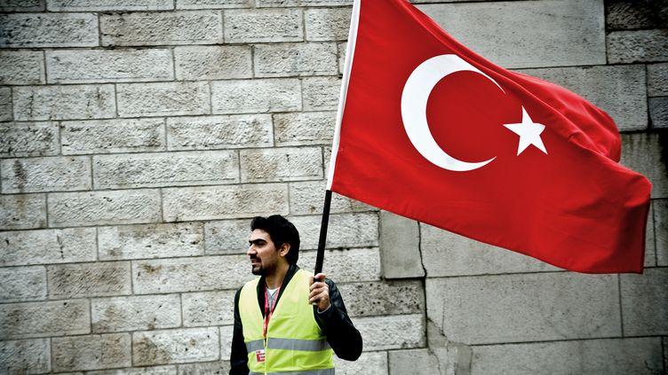 Un homme tient un drapeau turc lors d'une manifestation contre le projet de loi visant à réprimer la négation du génocide arménien, le 21 janvier 2012 à Paris. (NICOLAS MESSYASZ / CITIZENSIDE.COM)