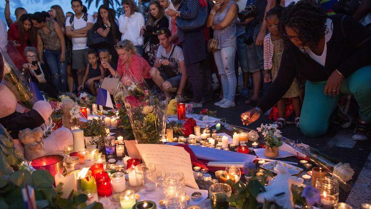 Des personnes rendent hommage aux victimes de l'attentat à Nice, le 15 juillet 2016. (IRINA KALASHNIKOVA / SPUTNIK / AFP)