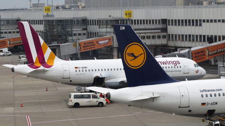 Des avions des compagnies aériennes allemandes Germanwings (à gauche) et Lufthansa à l'aéroport de Düsseldorf, le 27 mars 2015. (ALBERT GEA / REUTERS)