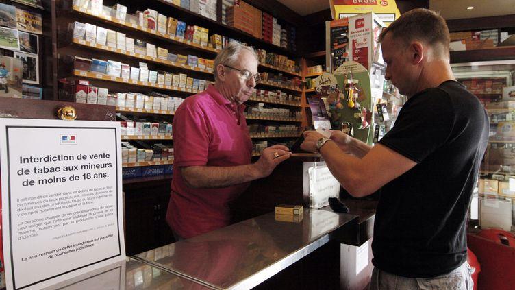 Un homme achète un paquet de cigarettes le 23 juillet 2010 dans un bureau de tabac à Paris. (AURORE MARECHAL / AFP)