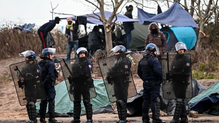 Des migrants dans un camp de fortune, le 28 novembre 2019, à proximité de Calais (Pas-de-Calais). (DENIS CHARLET / AFP)