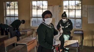 Une élève de l'école secondaire Sitoromo Junior à Sterkspruit, Afrique du Sud, prend du papier hygiénique pour nettoyer son bureau, le 6 juillet 2020. (MARCO LONGARI / AFP)