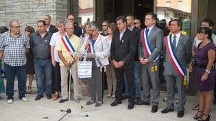 Des élus de Saint-Quentin-Fallavier (Isère), rassemblés devant l'hôtel de ville de la commune, le 27 juin 2015, au lendemain de l'attentat qui a visé une usine de la zone industrielle locale. (MARIUS BECKER / DPA / AFP)
