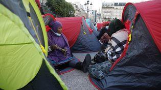 Des migrants installent des tentes devant l'Hôtel de Ville de Paris, le 24 juin 2021, lors d'une opération organisée par l'association Utopia56. (GEOFFROY VAN DER HASSELT / AFP)