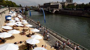 """Des passants se promènent sur les quais de Seine,lors du troisième jour de l'opération """"Paris plages"""", le 22 juillet 2015. (MIGUEL MEDINA / AFP)"""