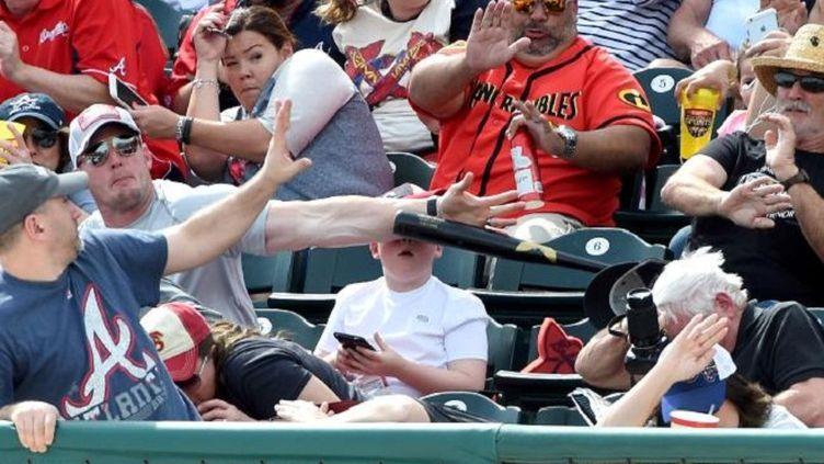 Un homme sauve un enfant d'une batte de baseball partie dans le public à pleine vitesse