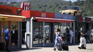 Des touristes devant des agences de location de voiture, à l'aéroport d'Ajaccio, Corse, le 9 juillet 2020. (PASCAL POCHARD-CASABIANCA / AFP)