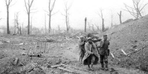 Durant la bataille du Chemin des Dames, en avril 1917, quatre militaires, dont un prisonnier allemand, portent un brancard avec un blessé à travers un paysage dévasté par la guerre. (AFP - Frantz Adam)