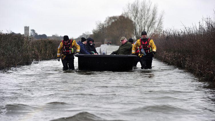 Des habitants de Muchelney (Royaume-Uni) quittent le village par bateau, le 31 janvier 2014. (CARL COURT / AFP)