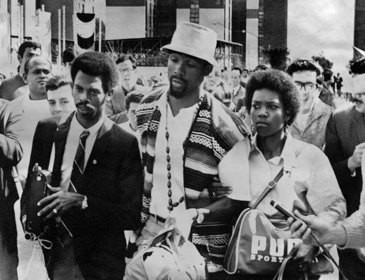 """John Carlos quitte le village olympique avec sa femme, après avoir été suspendu pour le geste du """"Black Power"""". (- / EPU)"""