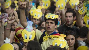 """Des étudiantsportent des masques représentant Titi, le célèbre canari jaune du dessin animé américain """"Titi et Grosminet"""", lors d'une manifestation favorable au référendum en Catalogne, le 28 septembre 2017, à Barcelone. (JOSEP LAGO / AFP)"""