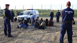 Des migrants arrêtés en Hongrie après avoir franchi la frontière illégalement, le 15 septembre. Ils risquent 3 ans de prison. (BERNADETT SZABO / REUTERS)