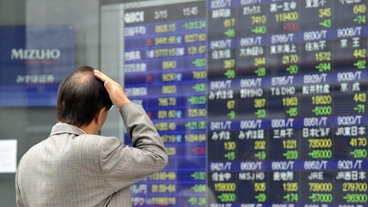 Un tokyoïte devant un tableau de changes. (AFP PHOTO / Yoshikazu TSUNO)