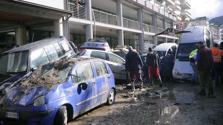 Des voitures empilées après une coulée de boue dans les rues d'Aulla en Toscane (Italie), le 26 octobre 2011. (FABIO MUZZI / AFP)