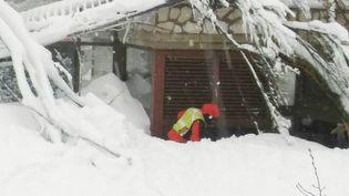 Un secouriste fouille l'entrée de l'hôtel engloutipar une avalancheàFarindola, au centrede l'Italie, le 19 janvier 2017 (REUTERS)