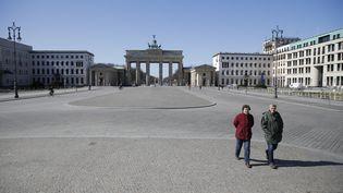 Deux passants devant la porte de Brandebourg à Berlin, le 23 mars 2020. (ODD ANDERSEN / AFP)