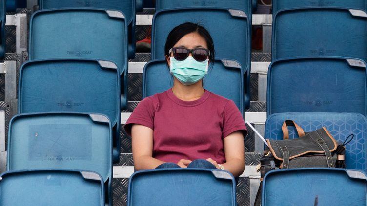 Une spectatrice regarde un entraînement pendant l'Open d'Australie, à Melbourne, le 15 janvier 2020. (ASANKA BRENDON RATNAYAKE / AFP)