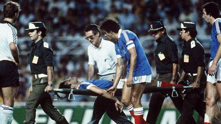Le défenseur français Patrick Battiston est emmené sur une civière après un choc violent avec le gardien allemand Harald Schumacher le 8 juillet 1982 lors de la demi-finale de Coupe du monde de football à Séville. Il est réconforté par le capitaine de l'équipe de France, Michel Platini. (AFP )