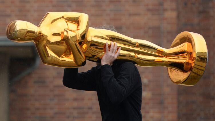 Un homme transporte une statue d'Oscar, à Potsdam (Allemagne), le 23 février 2015. (RALF HIRSCHBERGER / DPA / AFP)