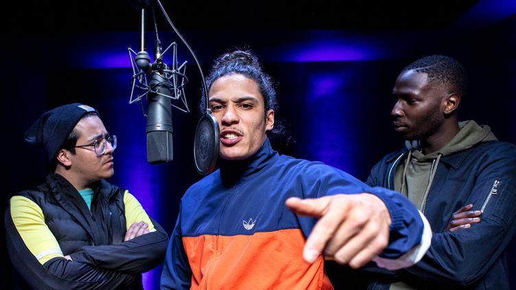 Le rappeur Hatik, au centre, interprète la jeune pépite APASH dans la série. (MANDARIN PRODUCTION)