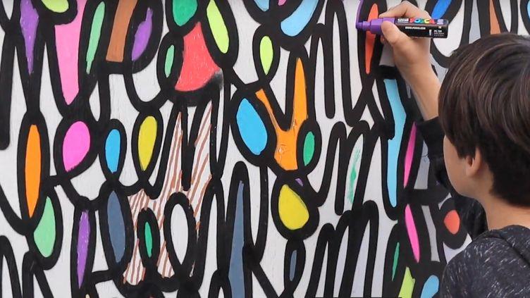 """La fresque imaginée par Arthur Simony est devenue un espace participatif pour tous ceux qui souhaitent redonner des couleurs à la rue de Trévise à Paris (PHOTO EXTRAITE DE LA VIDEO """"ACHETEZ DE L'ART"""")"""
