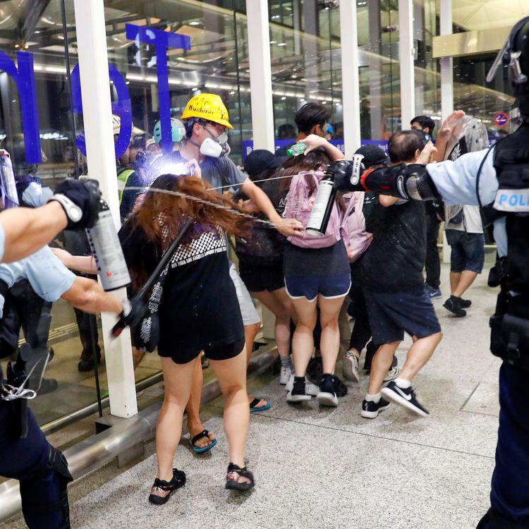 Les forces de l'ordre tentent de disperser des manifestants pro-démocratie, à l'aéroport international de Hong Kong, le 13 août 2019. (TYRONE SIU / REUTERS)