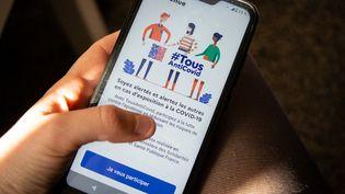Un utilisateur ouvre l'application TousAntiCovid, le 7 mai 2021, à Montpellier (Hérault). (SOLENE ARTAUD / HANS LUCAS / AFP)