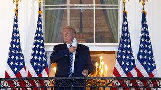Donald Trump retire son masque sur le balcon de la Maison Blanche le 5 octobre 2020 après avoir été hospitalisé durant trois jours, contaminé par le Covid-19. (WIN MCNAMEE / GETTY IMAGES NORTH AMERICA / AFP)