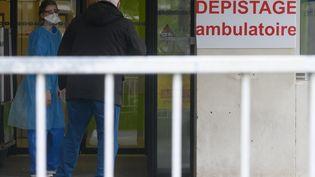 Un patient et une infirmière, équipée d'un masque de protection contre le coronavirus Covid-19, au CHU de Nantes (Loire-Atlantique), le 10 mars 2020. (ESTELLE RUIZ / NURPHOTO / AFP)