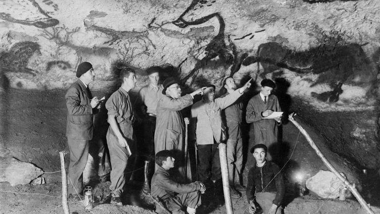 Le paléontologue et préhistorien français Henri Breuil observe le panneau des aurochs dans la salle des taureaux de la grotte de Lascaux en 1948 àMontignac en Dordogne, en compagnie d'autres archéologues et de deux des adolescents qui ont découvert la grotte Marcel Ravidat (D, assis) et Jacques Marsal (G, assis). (AFP)