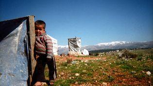 """Mohanad pose contre l'abri de fortune fabriqué par sa famille dans un campement deMarjaayoun, dans le sud du Liban. L'auteur de la photo est son grand frère Omar, âgé de 8 ans. Il a pris se cliché """"pour se souvenir de ce moment quand [sa] famille rentrera en Syrie"""". (UNICEF / ZAKIRA)"""