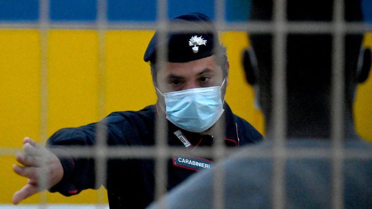 Un agent de sécurité italien devant des migrants dans un centre d'hébergement sur l'île de Lampedusa, le 14 mai 2021. (ALBERTO PIZZOLI / AFP)