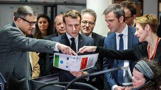 Le président Emmanuel Macron, le ministre de la Santé Olivier Véran en visite au centre d'appel du Samu de l'hôpital Necker, à Paris, le 10 mars 2020. (LUDOVIC MARIN / AFP)