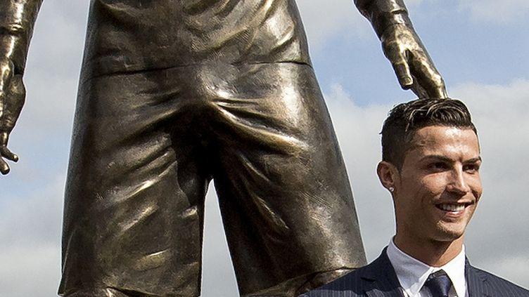 La photo de Cristiano Ronaldo, souriant, au côté de sa statue. (GREGORIO CUNHA / AFP)