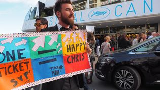 Un homme à la recherche d'une invitation pour les projections du Festival tient une pancarte, le 16 mai 2015, à Cannes. (MUSTAFA YALCIN / ANADOLU AGENCY / AFP)