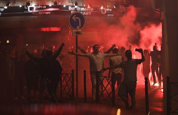 Des supporters anglais chantent après avoir allumé un fumigène, dans une rue menant du théâtre à la gare, mercredi 15 juin 2016, à Lille (Nord). (MARIUS BECKER / DPA / AFP)