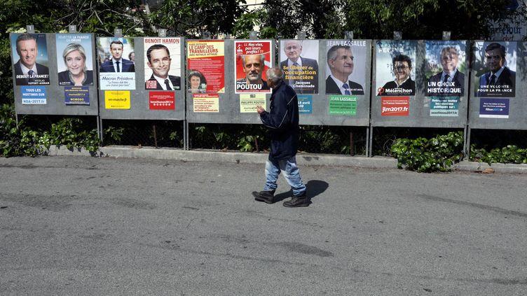 Un homme passe devant les panneaux électoraux dans la commune de Saint-André-de-la-Roche (Alpes-Maritimes), lundi 10 avril 2017. (ERIC GAILLARD / REUTERS)