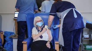 Une femme de 88 ans reçoit une dose de vaccin contre le Covid-19, à Hamilton (Ecosse), le 14 décembre 2020. (RUSSELL CHEYNE / POOL)