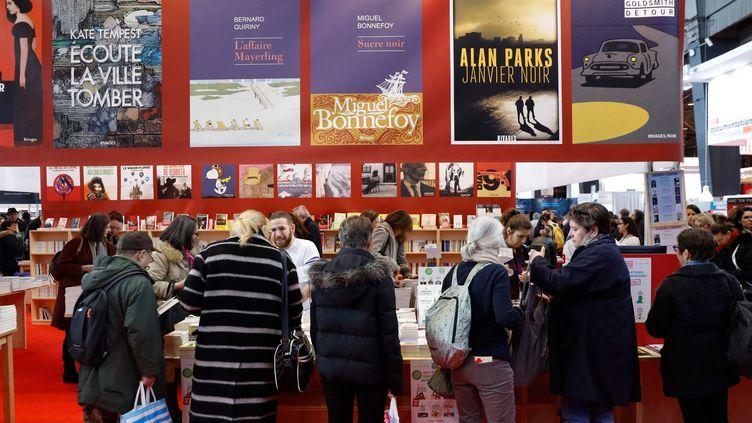 Des visiteurs s'arrêtent devant un stand du salon Livre Paris, le 16 mars 2018, à Paris. (PATRICK KOVARIK / AFP)