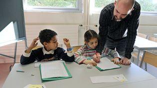 Un maître d'école corrige les exercices d'élèves de CP à l'école Arthur-Rimbaux d'Andrézieux-Bouthéon (Loire), le 29 novembre 2010. (PHILIPPE DESMAZES / AFP)