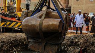Une partie d'une statue représentant peut-être Ramsès II est extraite d'une friche de la banlieue du Caire, le 13 mars 2017. (IBRAHIM RAMADAN / ANADOLU AGENCY)
