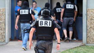 Le Raid à l'entrée de l'immeuble à Saint-Priest (Isère), où vivait l'homme suspecté d'être l'auteur de l'attentat de Saint-Quentin-Fallavier, vendredi 26 juin 2015. (PHILIPPE DESMAZES / AFP)