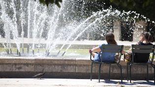 Deux personnes se rafraîchissent près d'une fontaine du Palais Royal, à Paris, mardi 30 juin 2015. (CAROLINE GARDIN / AFP)