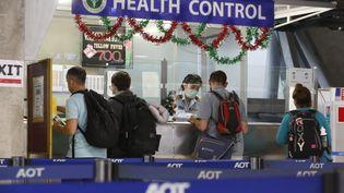 Des touristes font la queue aux contrôles sanitaires à l'aéroport à Bangkok en Thaïlande, le 5 janvier 2020. (PORNPROM SATRABHAYA / BANGKOK POST)