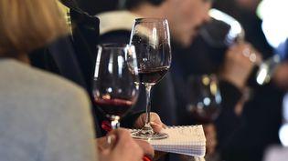 Des personnes goûtent différents vins. (GEORGES GOBET / AFP)