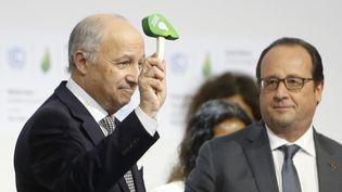 Laurent Fabius et François Hollande, quelques minutes après l'accord historique de la COP21, samedi 12 décembre 2015. (FRANCOIS GUILLOT / AFP)
