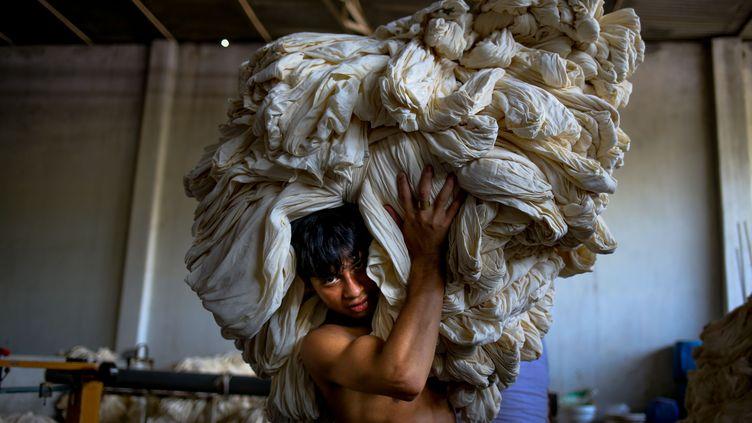 Un ouvriertravaille dans une usine de vêtements, le 8 septembre 2015, à Dacca (Bangladesh). (MOHAMMAD PONIR HOSSAIN / NURPHOTO / AFP)