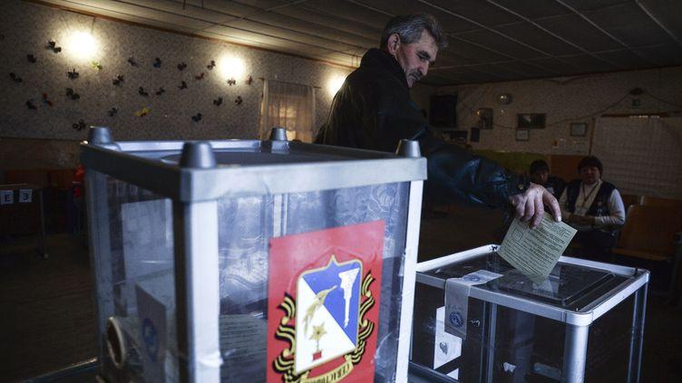 Un habitant de Crimée vote lors du référendum pour le rattachement de la péninsule à la Russie, le 16 mars 2014 dans le village deShirokoye. (VALERIY MELNIKOV / RIA NOVOSTI / AFP)