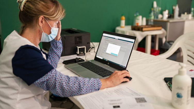 """Une professionnelle de santé consulte son ordinateur lors d'une opération de vaccination de travailleurs saisonniers au camping """"Le Floride"""" de Port-Barcarès (Pyrénées-Orientales), le 22 juillet 2021. (ALINE MORCILLO / HANS LUCAS / AFP)"""